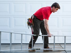 Male handyman with tool belt and ladder working outside. The background is a metal sectional garage doorOther related images
